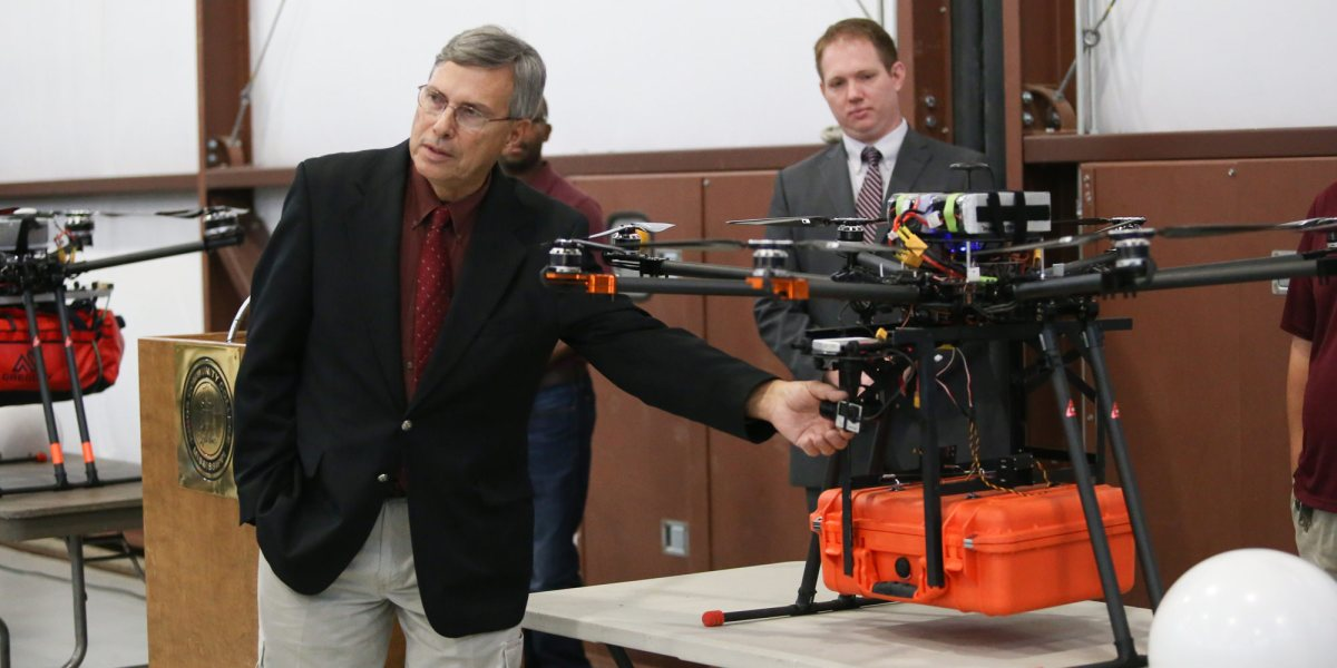 Dennis Lott, director of the Unmanned Aerial Systems program at Hinds Community College, points out a component on a UAV equipped with a telemedical package during a presentation Dec. 6 at John Bell Williams Airport to launch the Telemedical Drone Project. (Hinds Community College/April Garon)