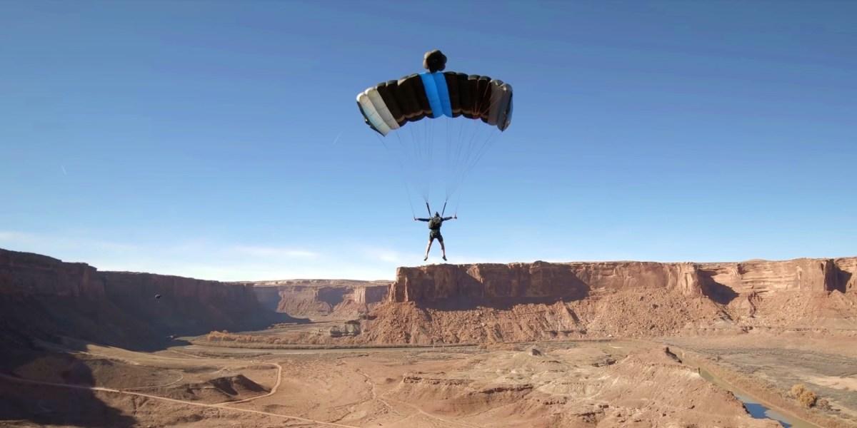 FPV drone flies in between parachute strings of BASE jumper